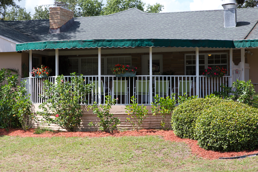 An image of the exterior of Curlew Care. It features a patio with a white railing, a green awning, and red flowers in window baskets.